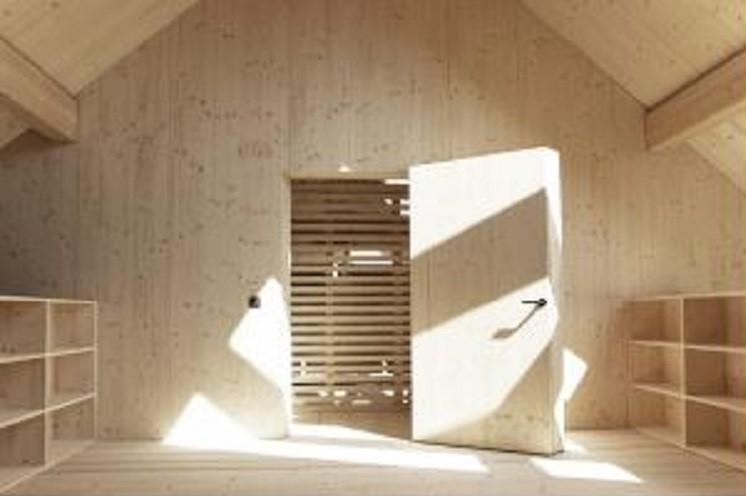 Tür zum Aufgang mit der zwischen die Lattenkonstruktion eingeschobenen Holzbohlentreppe