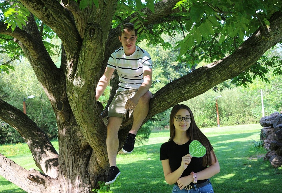 Junge sitzt auf einem Baum, Mädchen steht daneben