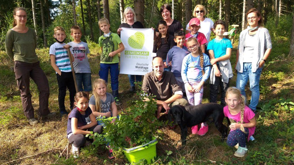 Kindergruppe bei Pflanzaktion im Wald