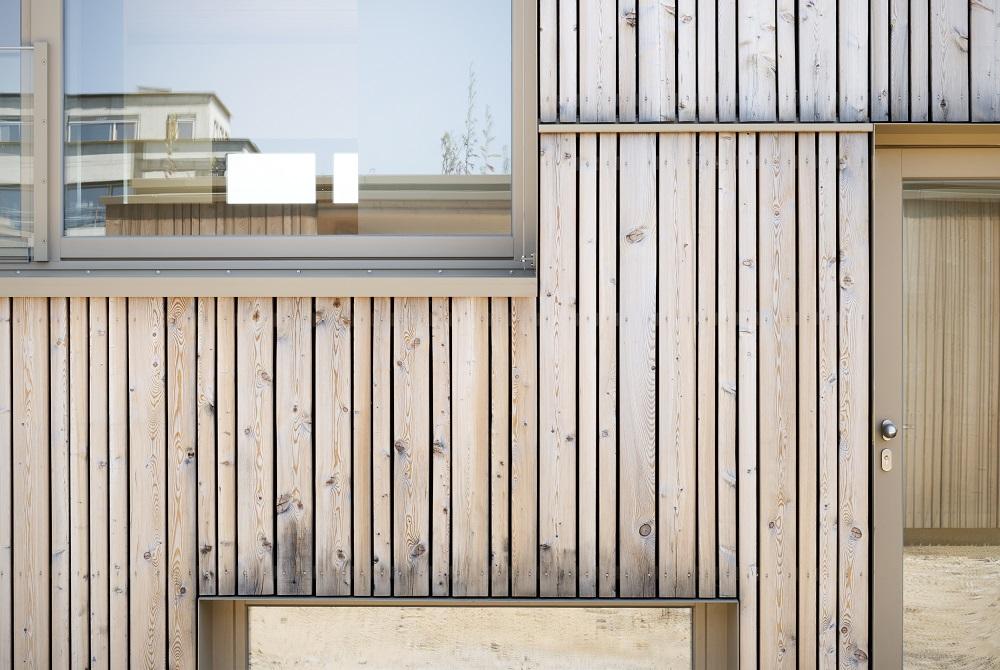 Fassade aus vertikalen Glattkantbrettern in unbehandelter sibirischer Lärche